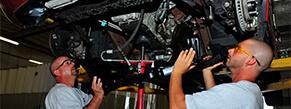 mechanics working on vehicle frame