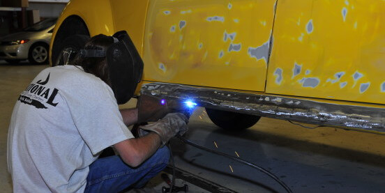 man doing metal work at national auto collision center